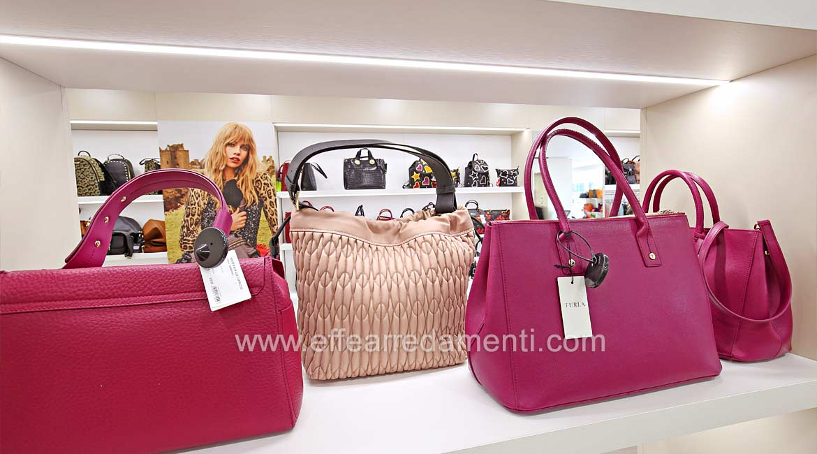 Furniture with illuminated compartment for display of Prada and Furla bags.